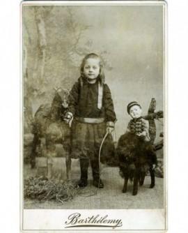 Jeune garçon aux anglaises en jupe un cheval en peau à la main et une poupée en militaire (Marcel Escudier)