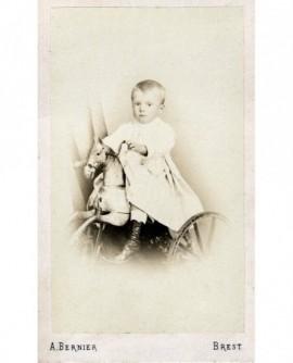 Enfant en robe en amazone sur cheval de bois-tricycle