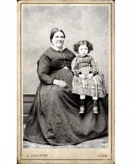 Femme forte assise, enfant en robe sur les genoux