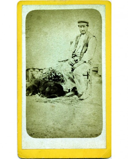 Homme du peuple en casquette assis, un chien à ses pieds.