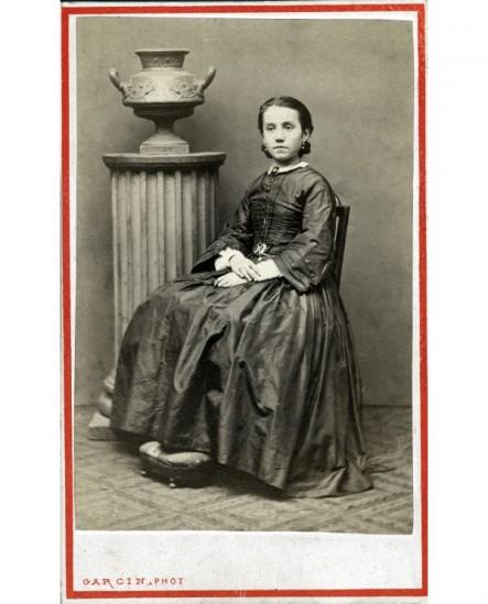 Femme en robe assise, colonne surmontée d\'un vase