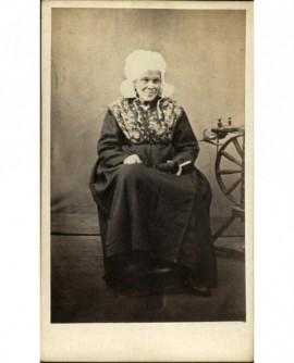 Femme âgée en coiffe assise, un rouet à pied près d'elle