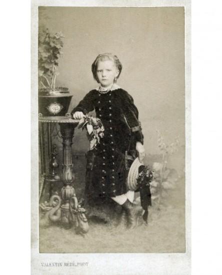 Fillette en robe de velours, bouquet et chapeau de paille