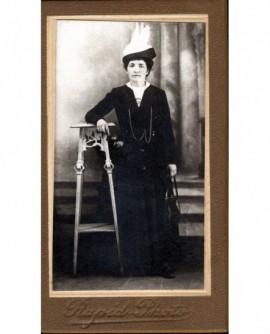 Femme en manteau et chapeau à toupet blanc appuyée à une console