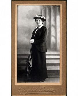 Femme en tailleur et chapeau fleuri appuyée sur ombrelle