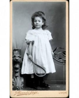 Fillette en robe blanche avec raquette (jouet)