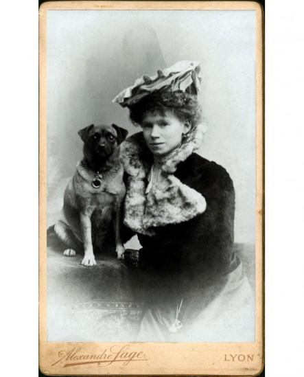 Femme en capeline et chien assis sur une table
