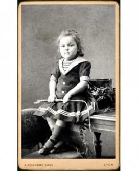 Fillette en robe marine, fouet à la main (jouet)