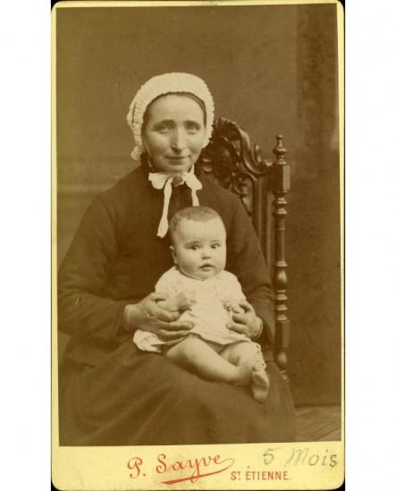 Jeune femme en coiffe assise, un bébé sur les genoux