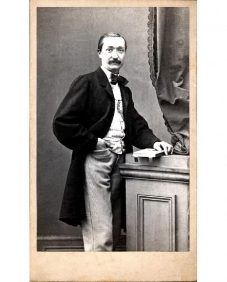 Homme moustachu debout, une main sur un livre