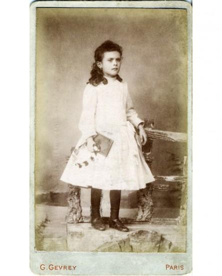 Fillette en robe blanche, couronne et livre à la main