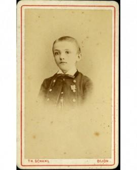 Portrait de jeune garçon, un insigne sur sa veste