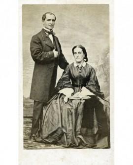 Couple : femme en robe assise, homme debout
