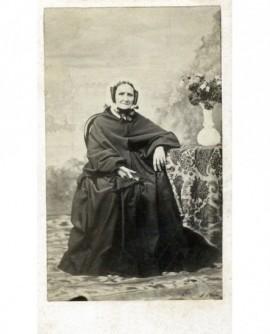 Femme en robe et mantelet noirs, coiffe blanche assise