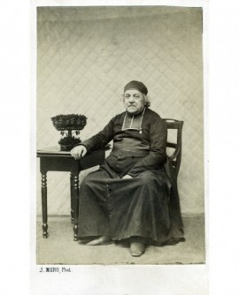 Ecclésiastique en rabat et bonnet sur la tête assis, accoudé à une petite table