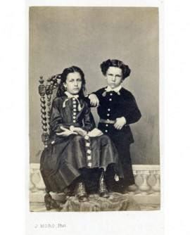 Frère debout et soeur (plus âgée) assise