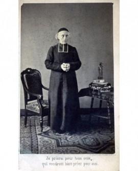 Ecclésiastique à cheveux blancs en calotte et rabat debout, mains jointes