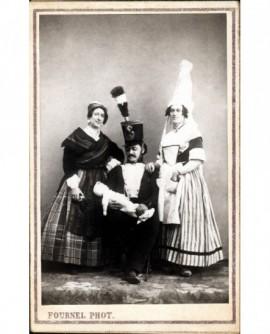 Trois personnes en costume de scène: grenadier assis tenant un poupon entre deux femmes debout