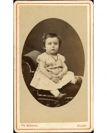 Bébé en robe courte assis sur un fauteuil