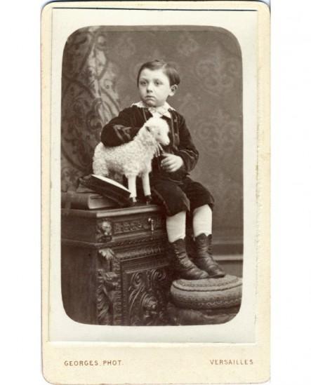 Jeune garçon tenant un mouton en peluche (jouet)