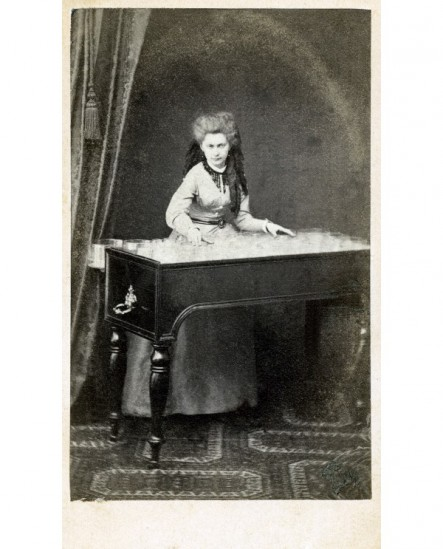 Femme posant devant un meuble musical emplie de pots de verre