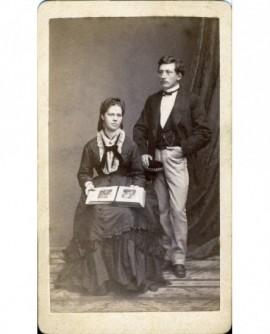Couple posant, lui debout, elle assise avec un livre de photographies