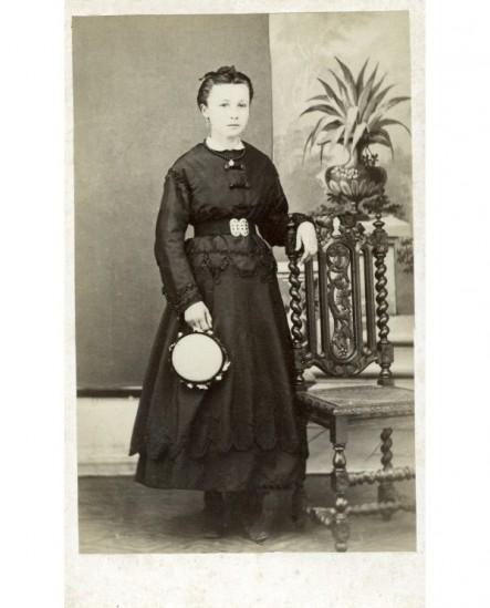 Jeune fille en robe noire, un tambourin à la main, accoudée à une chaise