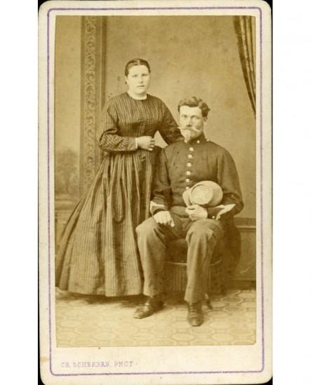 Couple: militaire assis, képi à la main, et femme debout
