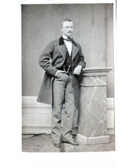 Homme posant debout accoudé à une stèle. Chaine de montre