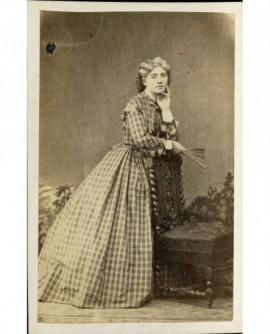 Jeune femme en robe à carreaux, accoudée à une chaise, un éventail à la main