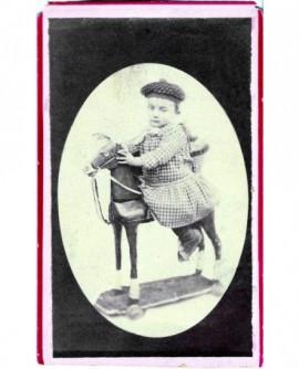 Enfant en sarrau et bonnet marin sur cheval de bois (jouet)