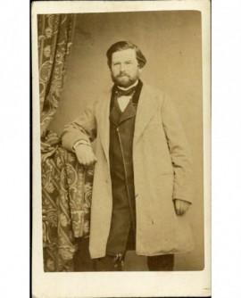 Homme barbu en manteau debout, accoudé