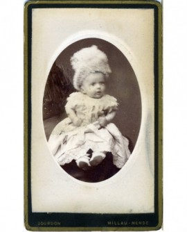 Bébé en robe et bonnet assis