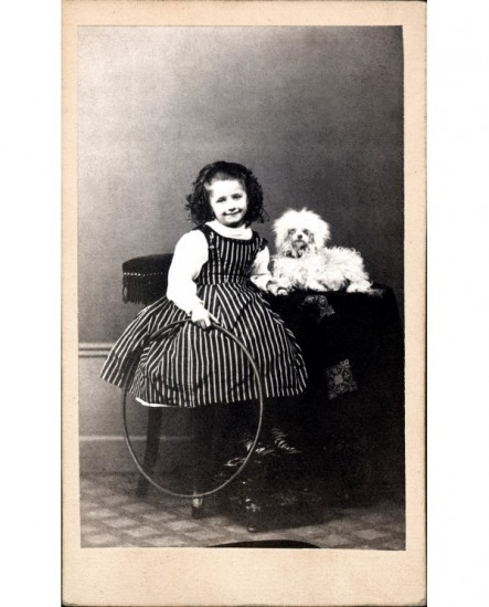Fillette assise, cerceau à la main, petit chien couché près d'elle