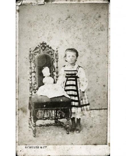 Petite fille avec poupée sur une chaise