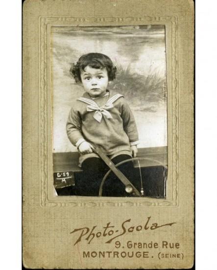 Garçon en veste de marin avec un jouet (crécelle à roue)