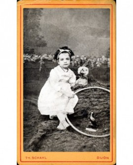 Fillette en robe assise un cerceau à la main, un chien en peluche (jouet)