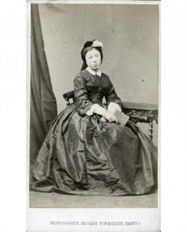 Femme en bonnet à fleurs assise livre à la main