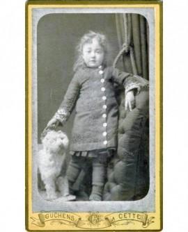 Fillette debout sur un fauteuil, tenant un chien à roulettes (jouet)