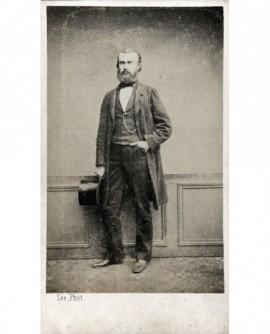 Homme barbu debout, chapeau à la main