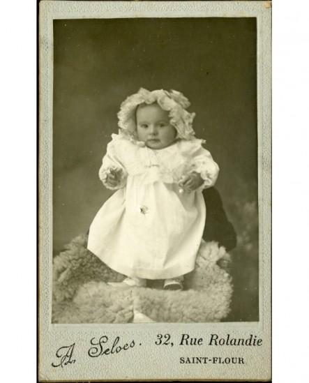 Bébé en robe et bonnet debout, sur une peau de mouton