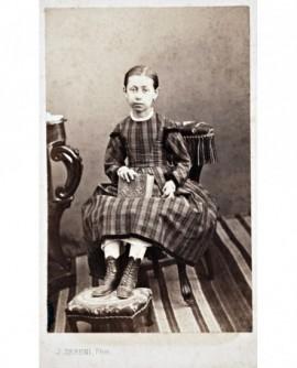 Fillette en robe assise tenant un album photo
