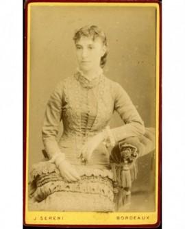 Jeune fille en robe à parements de dentelle, assise
