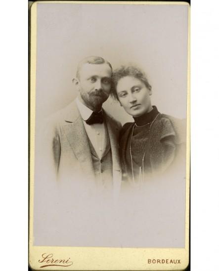 Couple, la tête penchée l'un vers l'autre (homme moustachu, femme avec sautoir)
