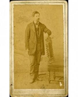 Homme moustachu debout, appuyé sur uen chaise