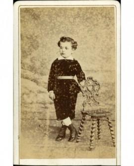 Petit garçon debout, pieds croisés, appuyé sur une chaise