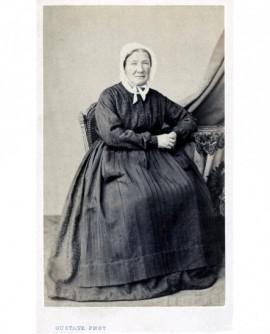 Femme agée en tablier sur sa robe et coiffe assise