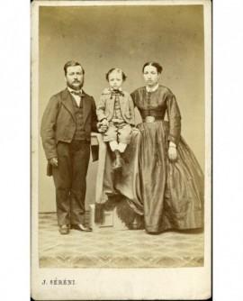 Portrait de famille: père et mère, leur fils entre eux perché sur une console