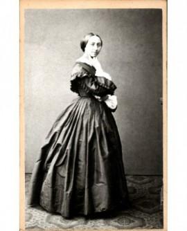 Femme debout, doigts appuyés contre la gorge