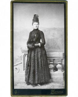 Femme en robe debout, les mains dans un manchon (institutrice)